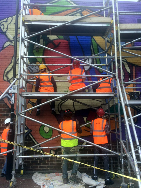 Students in Hi-Vis jackets on scaffold tower working on mural in Heald St